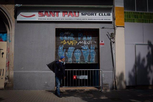 Un home sense llar surt del gimnàs social Sant Pau, a 28 d'abril de 2021, a Barcelona, Catalunya, (Espanya).