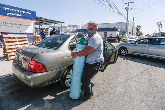 Archivo - Un hombre carga un cilindro de oxígeno en Queretaro.
