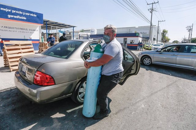 Archivo - 21 January 2021, Mexico, Queretaro: A man carries an oxygen cylinder as people line up to buy oxygen for their relatives infected with the coronavirus disease (COVID-19). Mexico faces a shortage of oxygen tanks and a fourfold rise in prices as c