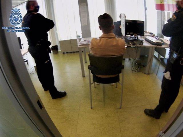 El detenido ante los agentes policiales