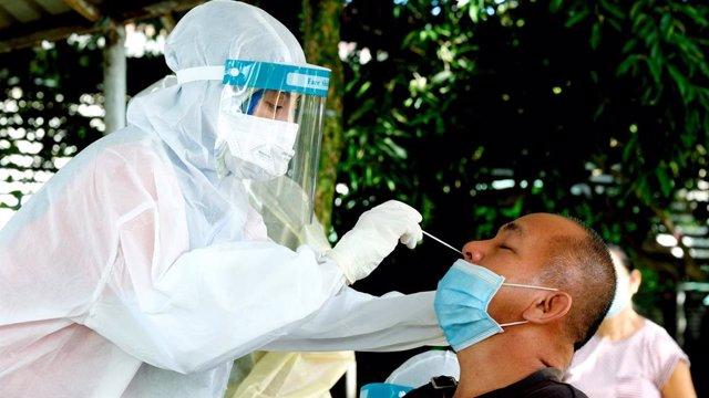 Archivo - Una trabajadora sanitaria toma una muestra a un hombre para un test de coronavirus en la ciudad malasia de Sandakan
