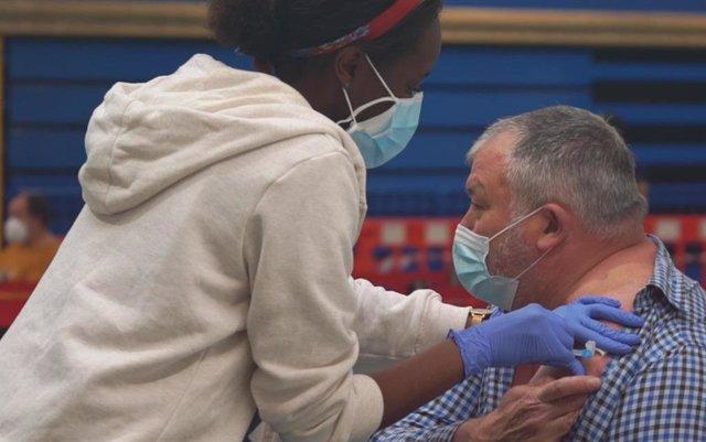 Una trabajadora sanitaria administra a un hombre la vacuna contra la COVID-19 en el polideportivo Germans Escalas, en Palma.