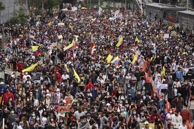 28 April 2021, Colombia, Bogota: People with face masks hold flags as they take part in a protest against a tax reform proposed by the government. Photo: Camila Diaz/colprensa/dpa