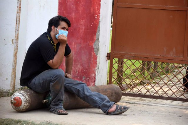 29 April 2021, India, Prayagraj: A man sits on medicated oxygen cylinders as he waits at a refilling plant in Prayagraj to refill them for a COVID-19 patient. Photo: Prabhat Kumar Verma/ZUMA Wire/dpa