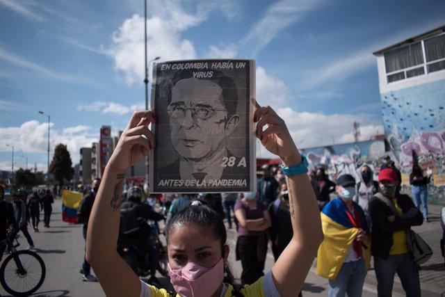 Una joven muestra un retrato contra el expresidente Álvaro Uribe durante las movilizaciones en contra de la reforma tributaria del Gobierno colombiano de Iván Duque.