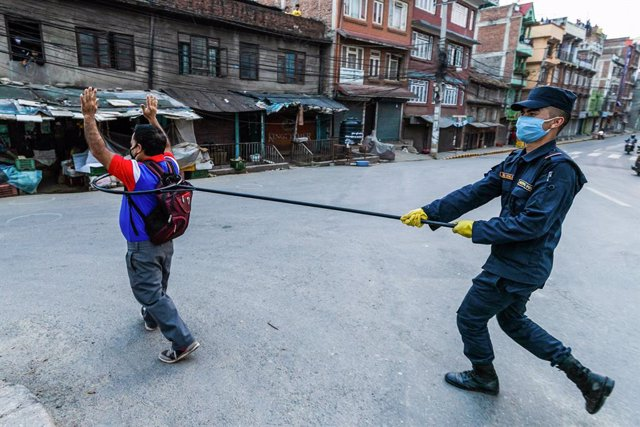 Archivo - FILED - 23 April 2020, Nepal, Kathmandu: A police officer keeps a safe distance as he detains a man violating the lockdown regulations aiming to curb the spread of the coronavirus (COVID-19). Photo: Prabin Ranabhat/SOPA Images via ZUMA Wire/dpa