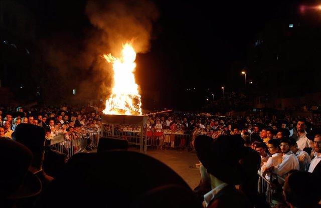 Archivo - Judíos ultraortodoxos encienden una hoguera durante una celebración de Lag BaOmer en Modi'in Illit, el 22 de mayo de 2019.