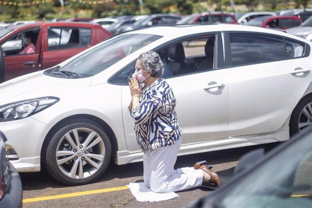 Archivo - Una mujer reza durante una eucartía celebrada en el parking del Hipódromo de los andes, en Bogotá, Colombia.