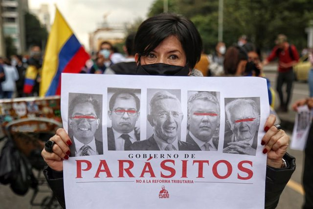 29 April 2021, Colombia, Bogota: A protester holds a placard says 'Parasites - No to Tax Reform' during a demonstration against the tax reform bill proposed by the government. Photo: Camila Díaz/colprensa/dpa