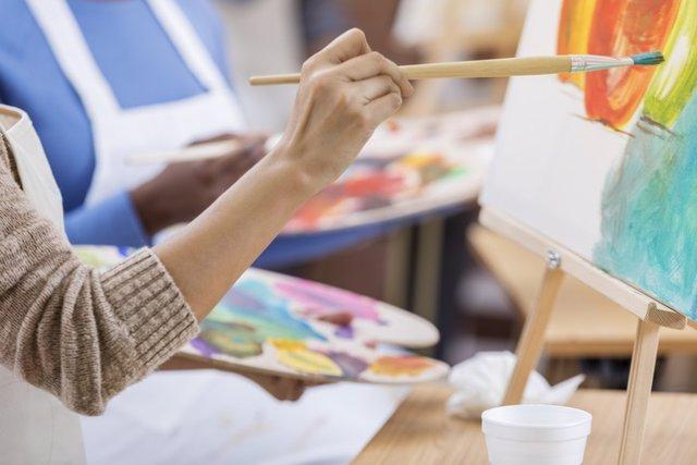 Archivo - Mujer trabaja en una pintura. Ella está usando un pincel mientras pinta sobre un lienzo. Ella sostiene una paleta. La gente está pintando de fondo.