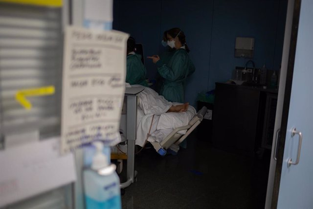 Archivo - Personal sanitario visita a un paciente ingresado en la Unidad de Cuidados Intensivos.
