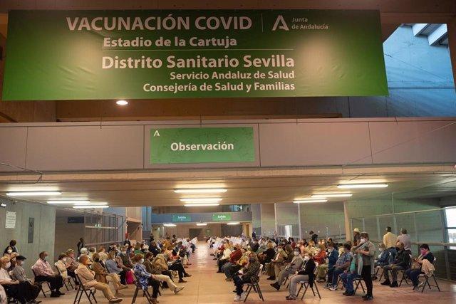 Varias personas esperan en el área de observación después de que les hayan administrada  la vacuna contra el Covid-19, a 28 de abril de 2021, en el Estadio de la Cartuja, en Sevilla, (España)
