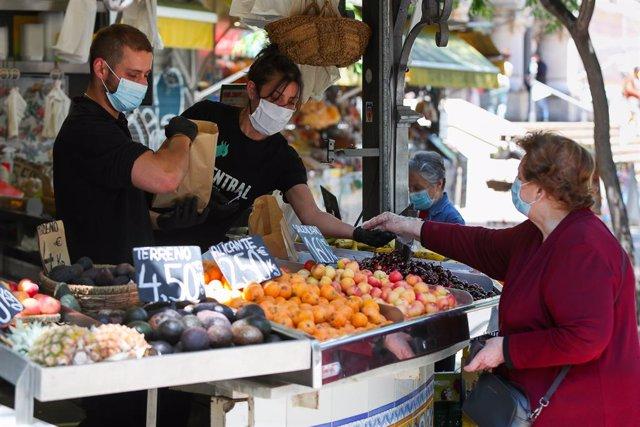 Archivo - Dos trabajadores de una frutería del Mercado Central de Valencia atienden a una clienta después de que el Ministerio de Sanidad autorizara a que la totalidad de la Comunidad Valenciana pasase en su conjunto a la fase 1 de la desescalada, en Vale