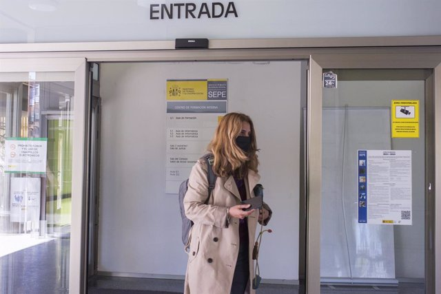 Una mujer entra por la puerta de una oficina del SEPE el día en el que se han conocido los datos de paro de marzo, a 6 de abril de 2021, en Madrid (España). El número de parados registrados en las oficinas de los servicios públicos de empleo (antiguo Inem