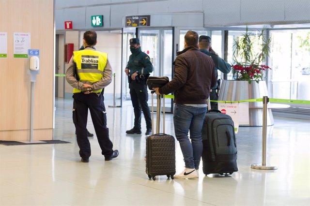 Archivo - Agentes de la Guardia Civil y empleados de seguridad vigilan a los pasajeros en el interior del Aeropuerto de Ibiza.