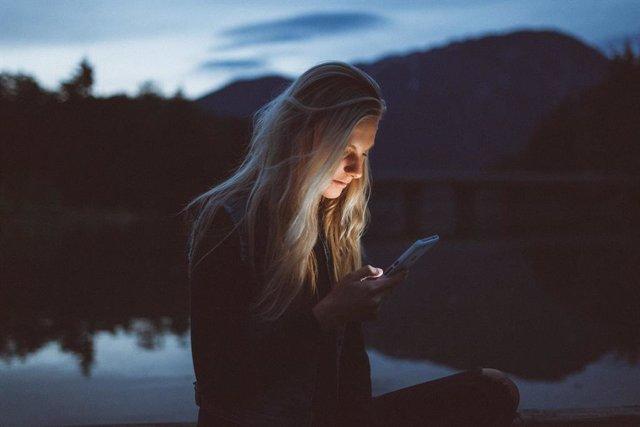 Mujer usa un móvil de noche.