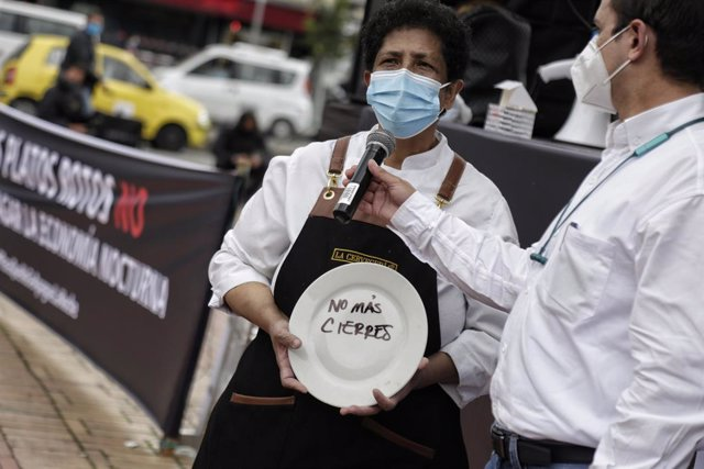 "26 April 2021, Colombia, Bogota: A woman holds a plate with words reads ""No more closures"", during a protest by restaurant and bar workers to demand support for the sector during the Coronavirus pandemic. Photo: Álvaro Tavera/colprensa/dpa"