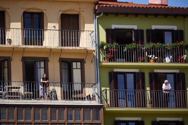 Archivo - Varias personas se asoman a sus balcones en Pamplona.