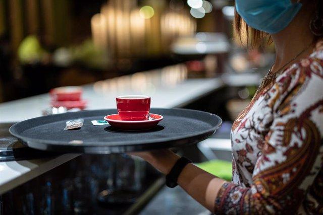 Archivo - Una trabajadora lleva un café a una mesa en una cafetería.