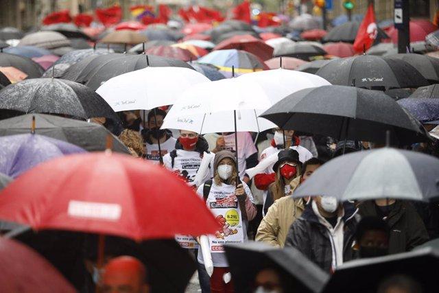 Manifestants amb mascarillas i paraigües en la concentració de Barcelona aquest 1 de Maig de 2021