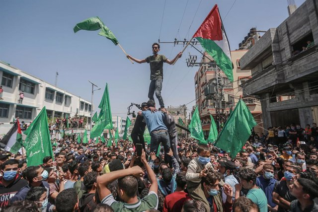 30 April 2021, Palestinian Territories, Jabalia: Supporters of the Palestinian Hamas Islamist movement wave flags during a demonstration against the postponement of Palestinian elections, which were supposed to be held on May 22nd. Palestinian President M