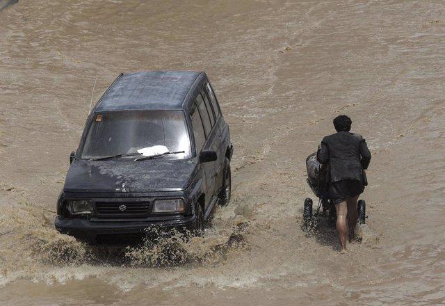 Archivo - FILED - 14 April 2020, Yemen, Sanaa: A man pushes his cart in a flooded street following heavy rains in Sanaa. Photo: Hani Al-Ansi/dpa