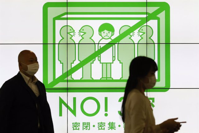 23 April 2021, Japan, Tokyo: Pedestrians wearing face masks walk past a screen showing measures to prevent the spreading of the new coronavirus after the Japanese Prime Minister Yoshihide Suga declared a state of emergency for Tokyo and the prefectures of