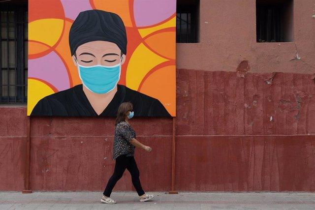 Una persona camina frente a un mural en homenaje a los trabajadores sanitarios durante la pandemia en Santiago, Chile.