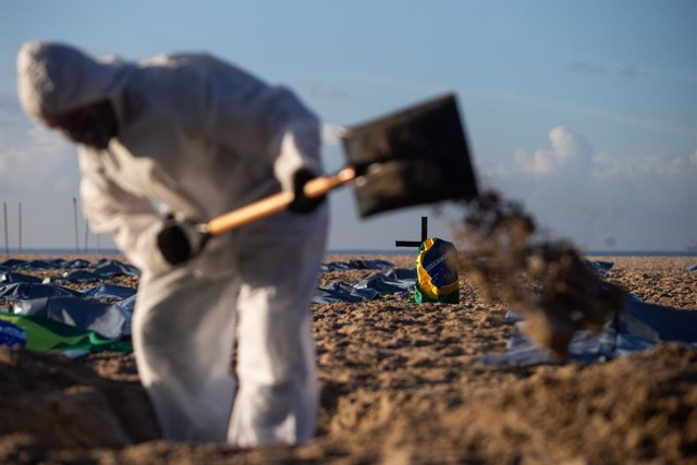 """30 April 2021, Brazil, Rio De Janeiro: Members of the NGO """"Rio de Paz"""" symbolically perform a funeral on Copacabana beach after the most populous country in Latin America passed the mark of 400,000 confirmed deaths related to Coronavirus (Covid-19). Photo"""