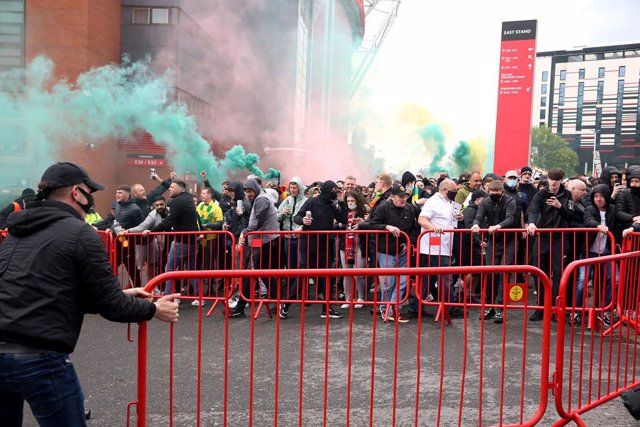 02 May 2021, United Kingdom, Manchester: Fans move barriers outside the ground as they let off flares whilst protesting against the Glazer family, owners of Manchester United, before their English Premier League soccer match against Liverpool at Old Traff