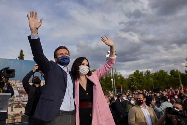 El presidente del PP, Pablo Casado y la presidenta de la Comunidad de Madrid y candidata a la reelección, Isabel Díaz Ayuso saludan a su llegada al último acto de campaña del partido, en el barrio de Salamanca