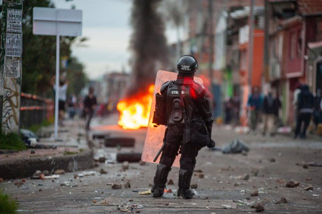 30 April 2021, Colombia, Bogota: A riot police officer stands behind burning tiers during clashes at a protest against the tax reform bill proposed by the government. Photo: Chepa Beltran/VW Pics via ZUMA Wire/dpa