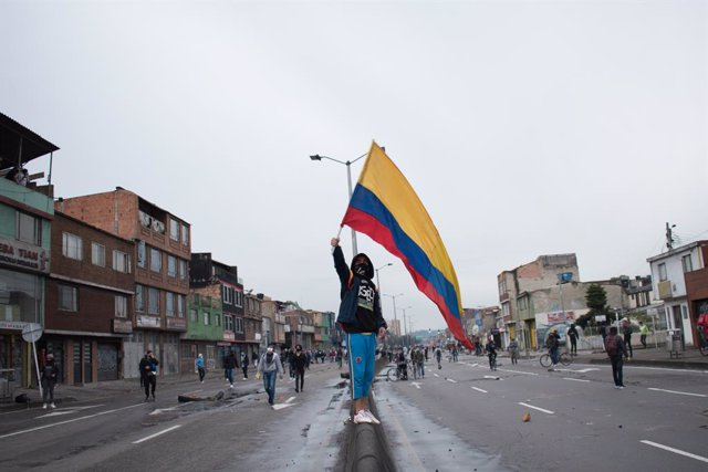 30 April 2021, Colombia, Bogota: A protester wave the Colombian flag during clashes with riot police at a protest against the tax reform bill proposed by the government. Photo: Daniel Santiago Romero Chaparro/LongVisual via ZUMA Wire/dpa