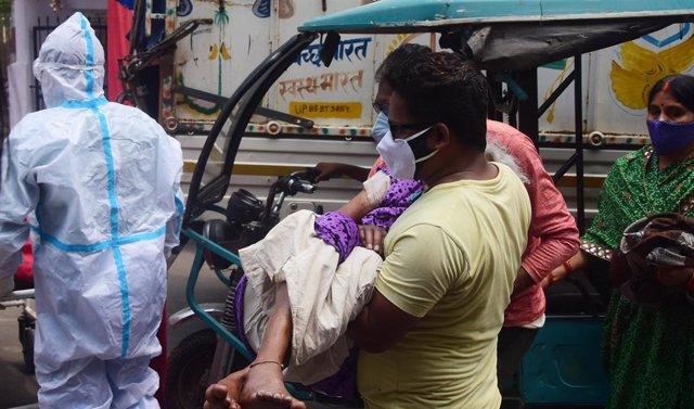 Un hombre lleva a un paciente de coronavirus en India.