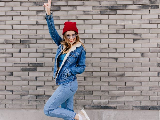 Archivo - Slim girl in trendy jeans having fun on the street in cold spring day. Blissful female model in denim attire dancing on urban background and waving hands.