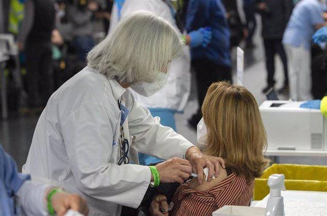 Una trabajadora sanitaria administra la primera dosis de la vacuna AstraZeneca contra el Covid-19 a una persona en el Wizink Center, a 9 de abril de 2021, en Madrid, (España). El dispositivo, puesto en marcha este viernes por la Comunidad de Madrid y coor