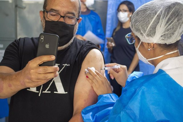 05 April 2021, Brazil, Sao Paulo: A police officer takes a selfie while being vaccinated against COVID-19 during a campaign to vaccinate police officers in Sao Paulo. Photo: Leco Viana/TheNEWS2 via ZUMA Wire/dpa