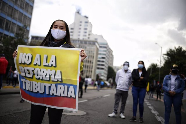 """28 April 2021, Colombia, Bogota: A demonstrator wearing a face mask holds a placards says """"No to tax reform"""" during a protest against a tax reform proposed by the government. Photo: Sergio Acero/colprensa/dpa"""