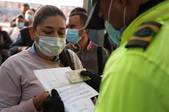 Un policía registra los documentos de una ciudadana para permitirle el acceso a un comercio en etapa de restricciones por coronavirus en Bogotá.