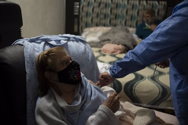 Archivo - 18 February 2021, Mexico, Mexico City: An elderly woman is vaccinated with a dose of AstraZeneca coronavirus vaccine at her home. City medical workers come to an elderly residence to administer people who do not have the opportunity to visit vac