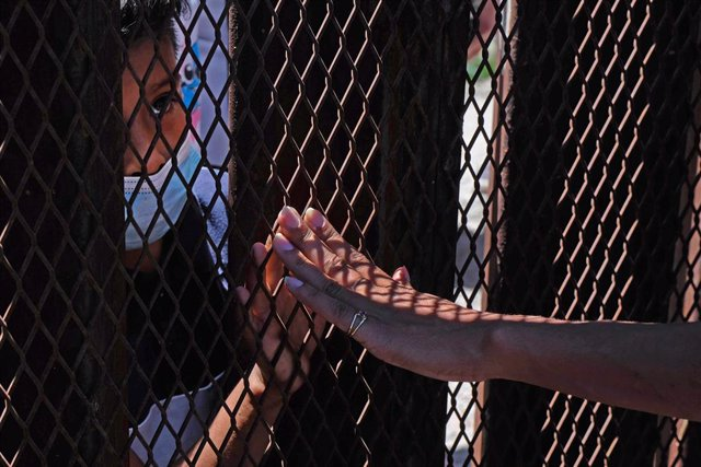 30 April 2021, US, Nogales: A supporter touches the hand of a young asylum-seeking migrant from behind the fence at border wall separating the United States and Mexico. Photo: Christopher Brown/ZUMA Wire/dpa