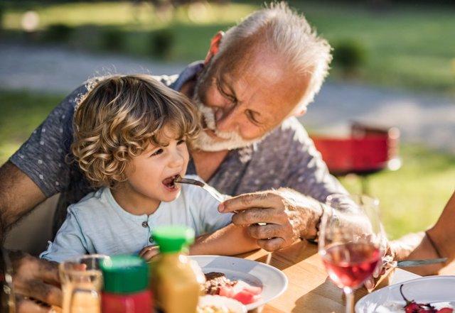 Archivo - Abuelo y nieto comiendo.
