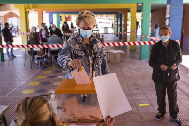 Una mujer ejerce su derecho a voto a la hora de comer en el Colegio Público Asturias en el distrito Puente de Vallecas