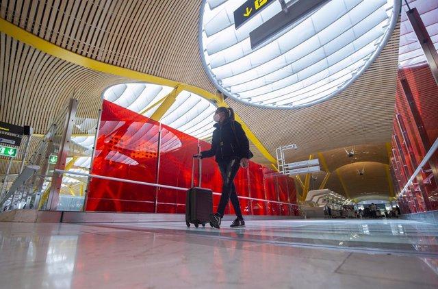 Archivo - Una pasajera desplaza su maleta por las instalaciones de la T4 del Aeropuerto Adolfo Suárez Madrid-Barajas, en Madrid (España), a 26 de marzo de 2021. Un total de 4.818 efectivos de las Fuerzas y Cuerpos de Seguridad del Estado (FCSE) se despleg
