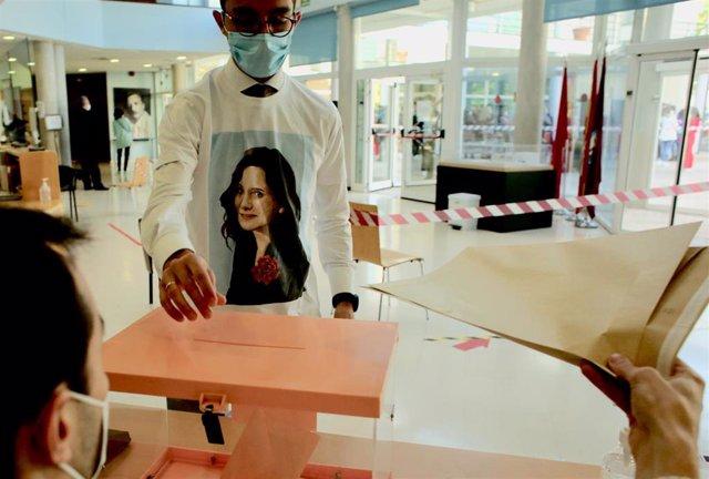 Un hombre acude a votar con una camiseta de Isabel Díaz Ayuso en el Centro cultural Alfredo Krauss.