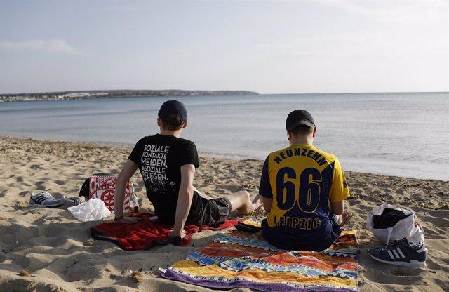 Archivo - Dos turistas alemanes en la playa del Arenal, a finales de marzo.