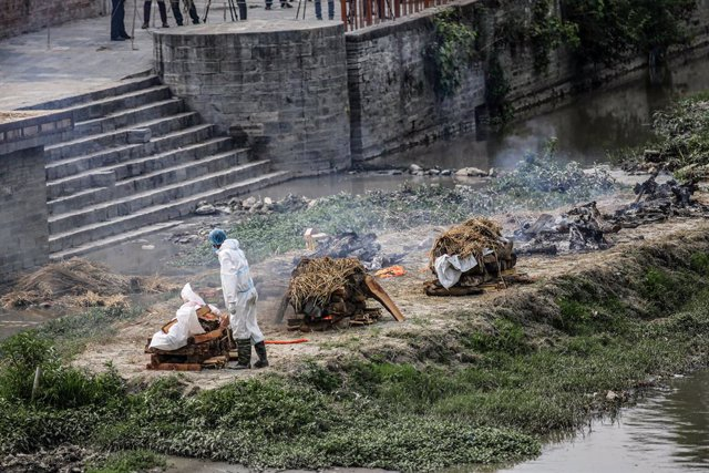 03 May 2021, Nepal, Kathmandu: A worker wearing personal protective equipment (PPE) cremates the body of a COVID-19 victim on the bank of Bagmati River. The Nepalese government banned all domestic and international flights until 14 May in an attempt to st
