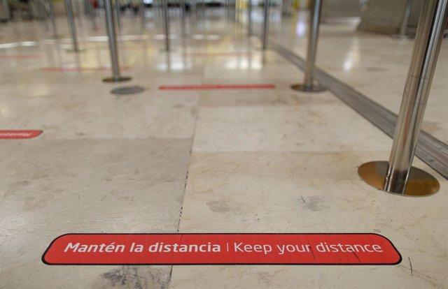 Archivo - Cartel de aviso de seguridad para preservar la distancia pegado en el suelo de la Terminal T4 del Aeropuerto Adolfo Suárez Madrid-Barajas, que junto con el Josep Tarradellas Barcelona-El Prat, Palma de Mallorca y Gran Canaria participará en la p