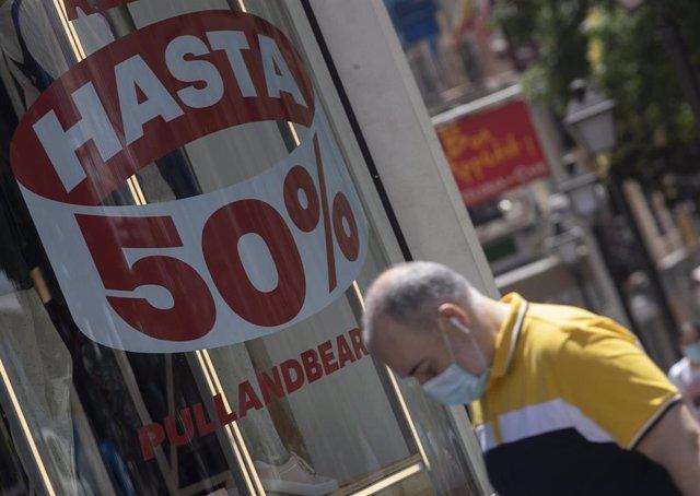 Archivo - Una persona pasa al lado de un escaparate de una tienda de la capital con carteles de descuentos durante el segundo día de rebajas, en Madrid (España), a 26 de junio de 2020.