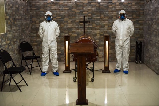 12 April 2021, Chile, Temuco: Lar de Cristo Funeral Home staff are seen dressed in full protective suits as they stand next to a casket. The funeral home reported a 20 percent increase in funeral services in the wake of the Coronavirus pandemic. Photo: Ma